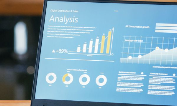 Business person looking at their laptop on a desk with an analytics dashboard on the screen