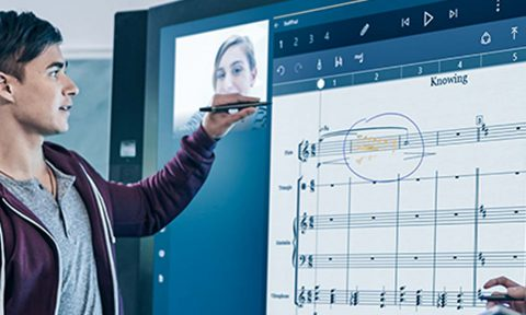Student using Surface Hub in class with lecturer watching on