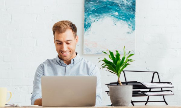 Man sat happily working in his gome office