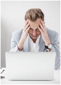 Man in dispair looking at his laptop