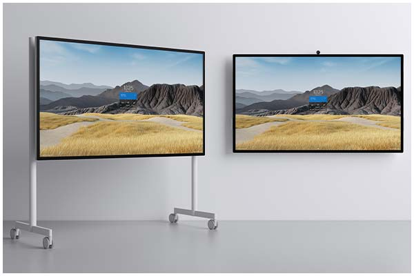 Two Microsoft Surface Hub 2s devices, one wall mounted and one on a stand