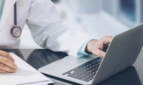 Close up of a doctor working on a laptop