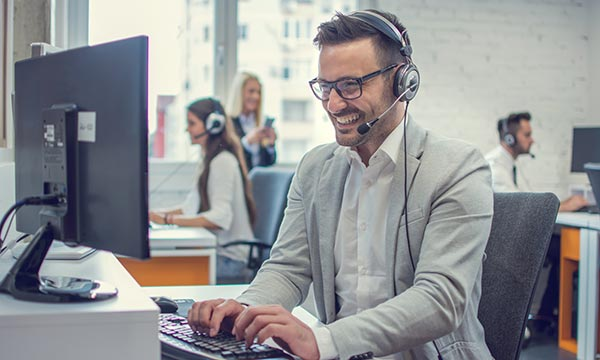 man with headset smiling at laptop