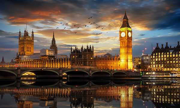 Westminster Palace and the Big Ben clocktower by the Thames river just after sunset