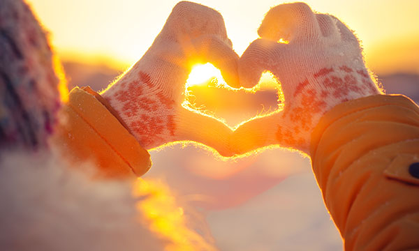 Image of a woman holding her hands up to the sunset while making a love heart with her fingers