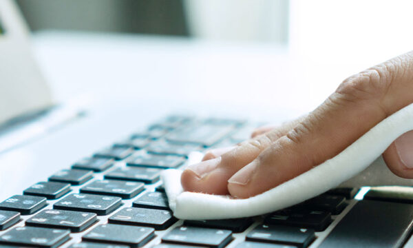 Image of a person cleaning the keyboard of a laptop