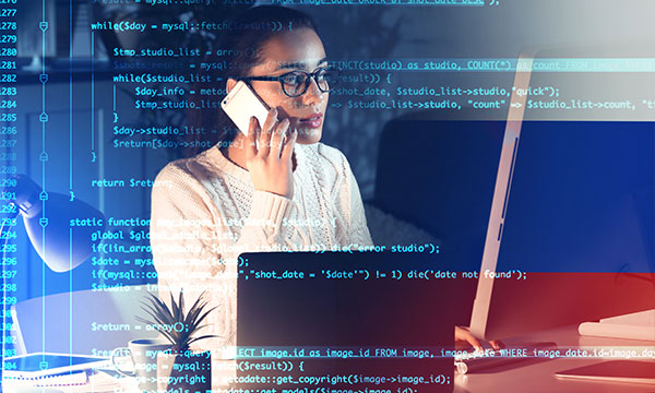 A woman on the phone at her desk with a data overlay