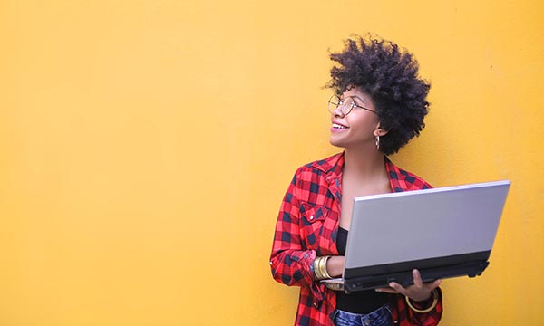 Student look up with a laptop in her arms with a bright yellow background