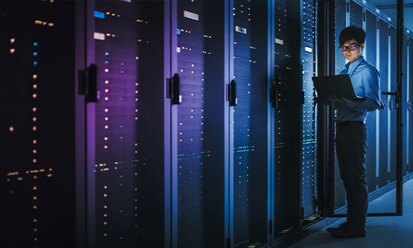 It technician looking inside a row of servers in a data center