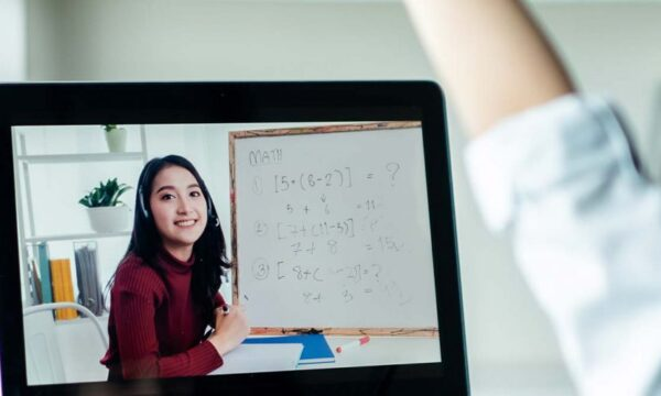 Young girl raising her hand in an online lesson