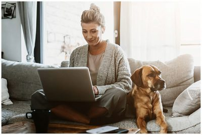 Woman working on her laptop while sat on the sofa with her dog
