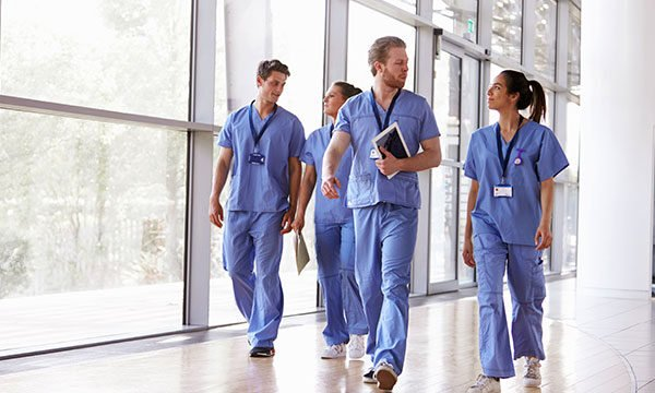 Group of doctors walking down a hospital hallway