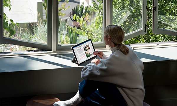 Woman sat working on a Microsoft Surface Device while looking out of the window