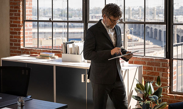 Business man walking up and down his office while using a Microsoft surface device