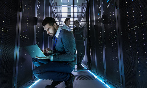 IT engineer looking at servers in a data center with a laptop in his hands