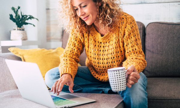 women with yellow jumper working on laptop with cup of coffee