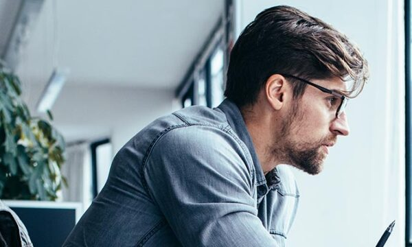man looking serious at computer in office