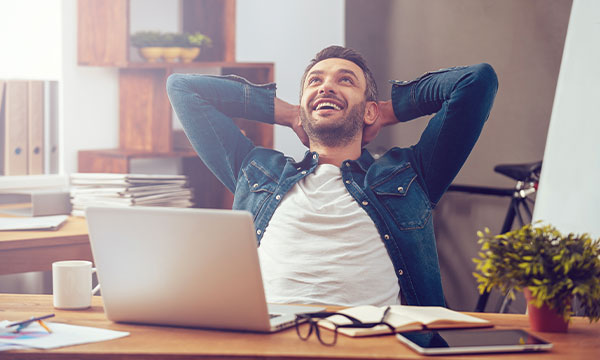 Man sat n a home office with his arms behind his head while looking up smiling