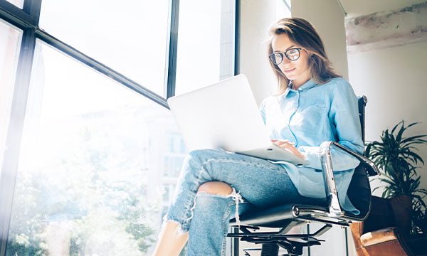 Woman sat on an office chair working on a laptop