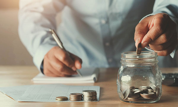 Man managing finances by making notes and putting a coin in a jar