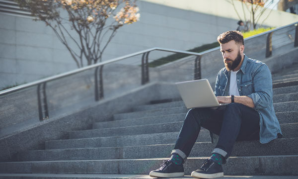 Image of a student working on a laptop alone on an empty outdoor staircase