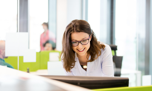 woman smiling while working on computer