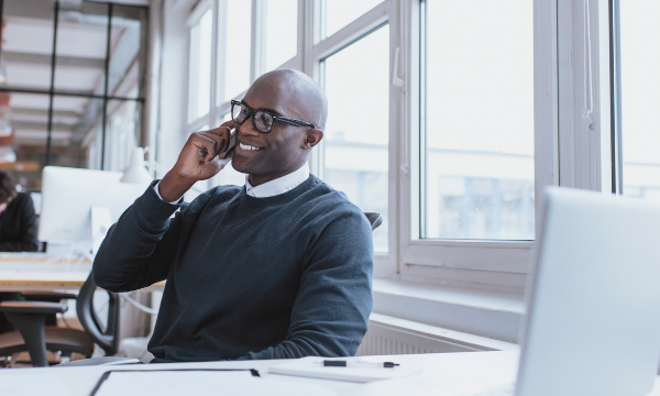 man working in office while smiling on phone