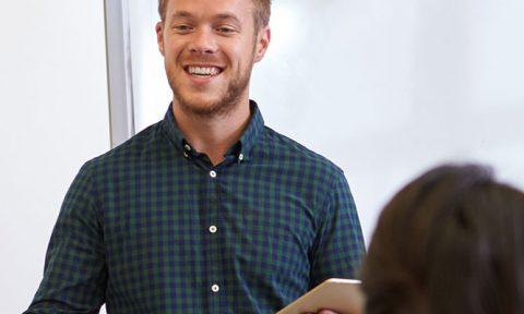 male teacher with tablet teaching class
