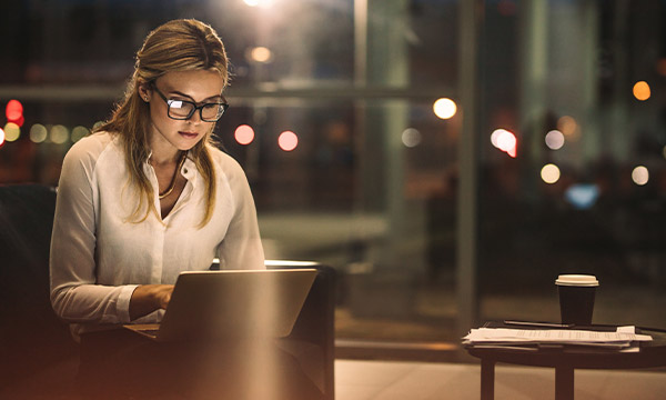 Young woman working on a laptop late at night