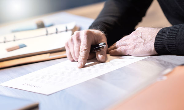 Senior businessman reviewing terms of contract at office