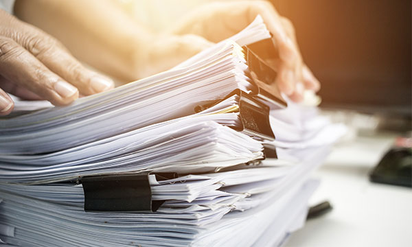 Businessman hands working in Stacks of paper files for searching information