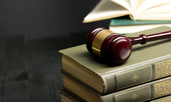 Open law book with a wooden judges gavel on table in a courtroom