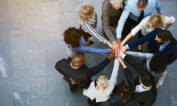 High angle view of a team of united coworkers standing with their hands together in a huddle